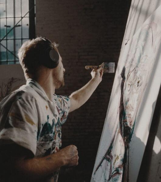 Artist painting in his studio listening to music through his black headphones