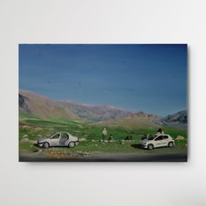 Two parked cars and few people sitting in the dirt staring into the mountain landscape