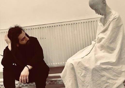Vasil Berela sitting in his studio staring at his sculpture of a sleeping woman