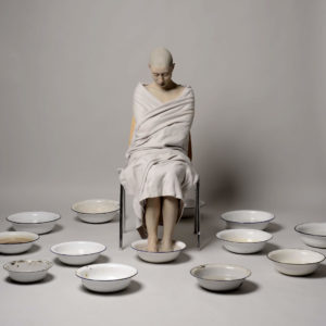Scultpure of a naked woman with shaved head and eyes closed covered in white fabrics sitting on a chair with her feet bathing in an enamal bowl