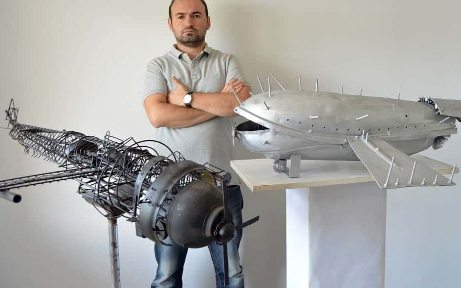 Romeo Melikyan wearing blue jeans and grey shirt standing in front of his sculptures flying objects